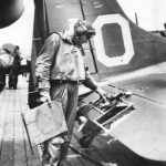 Lt James K. Brothers of VB-9 inspects damage to his SBD Dauntless