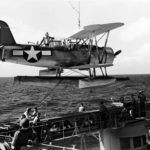 Floatplane Curtiss SOC is lowered onto the port catapult of USS Minneapolis (CA-36) during Wake Raid – 5 October 1943