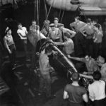 Crew loading torpedo on TBF aboard aircraft carrier 1943