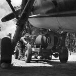 Marine Ordnancemen load 2000 lb bomb into the bomb bay of a Grumman TBF Avenger, 1944
