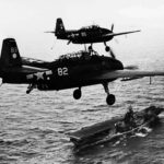 TBM-3 Avengers 82 and 95 of VT-2 with wheels and arrester hooks down above the carrier USS Hornet (CV-12) after a strike on Guam July 18 1944