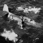 """TBF Avenger """"5"""" of VT-31 scrambles from the sinking aircraft after the pilot ditched it during flight operations on board the light carrier USS Cabot (CVL-28) on September 6, 1943"""