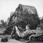 soldier reads newspaper by camouflaged