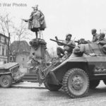 9th Army Troops in M8 passing statue in Moers Germany 1945