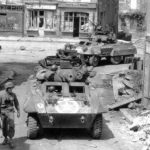M8 of Company C, 82nd Recon Battalion, 2nd Armored Division pass through the road junction at St. Sever Calvados