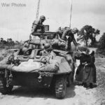 US Troops in M8 Greyhound stopped by hungry women in Periers 1944