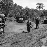 Soldiers and chained up trucks with trailer muddy road Bougainville 1944