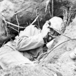 Iwo Jima Marine in foxhole on radio