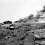 Marines shelter by LVT Amtrac hit by Japanese fire on Iwo Jima