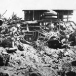 Marines take shelter behind an overturned Japanese truck