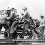 Wounded Marine gets transfusion loaded on LST