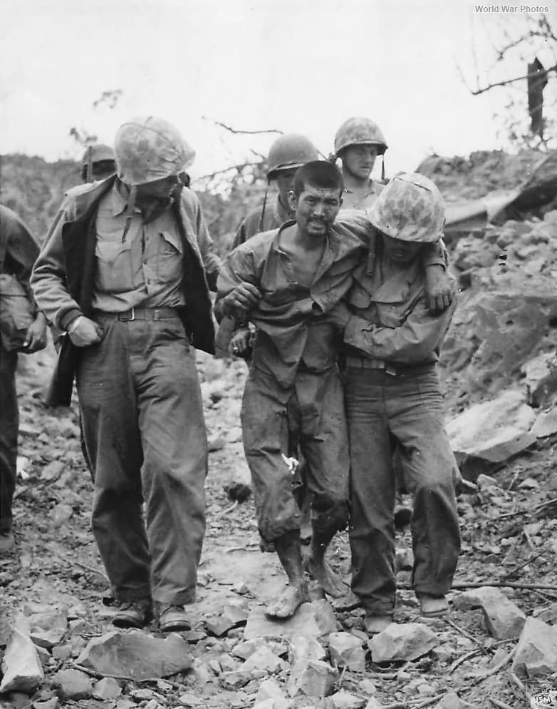 Marines help wounded Japanese Prisoner on Iwo Jima