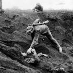 Marine approaches a Japanese soldier on Iwo Jima
