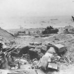 Troops on Iwo Jima Beach viewed over KOd Japanese gun position