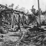 US Troops move thru ruins of Japanese warehouse on Makin