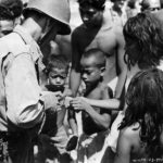 US officer of the 165th Infantry cuts up a piece of canned meat for hungry children