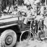 Soldiers in Jeep and on bicycle on newly captured Makin Atoll