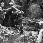 US 10th Army rifleman with the 32nd Infantry 7th Division searches a Japanese prisoner who has just emerged from a cave on Okinawa