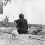 Coast guardsman with M1 carbine guards beach Saipan 1944