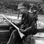 Marine examines a wooden dummy Japanese rifle used on Saipan