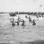 US Marines wade ashore on Tinian from landing barges, blocked by reefs 1944
