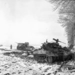 Destroyed M18 and M15 Halftrack in the background. Bastogne, December 29, 1944