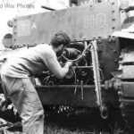Marine tank crewman checks M2A4 engine on Guadalcanal 1942