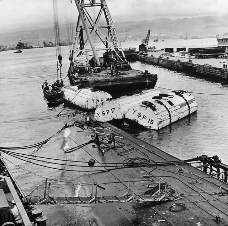 Salvage crews work to raise the minelayer USS Oglala which was sunk during Japanese attack on Peral Harbor 1942.