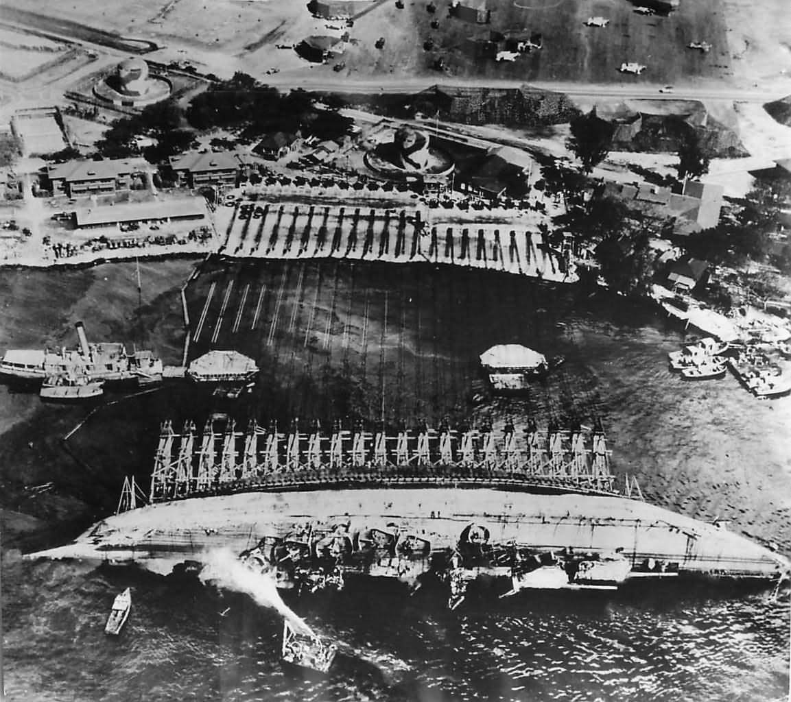 Crew work in Pearl Harbor to right the battleship USS Oklahoma ...
