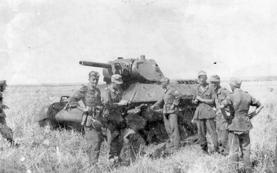 Wehrmacht soldiers next to a tank T-34 model 1941