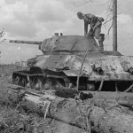 A german soldier stands on the top of a captured T-34/76 tank